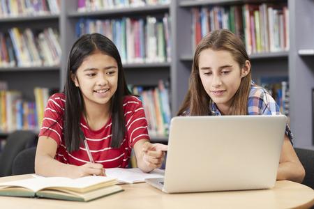 Deux lycéennes travaillant à l'ordinateur portable dans la bibliothèque Banque d'images