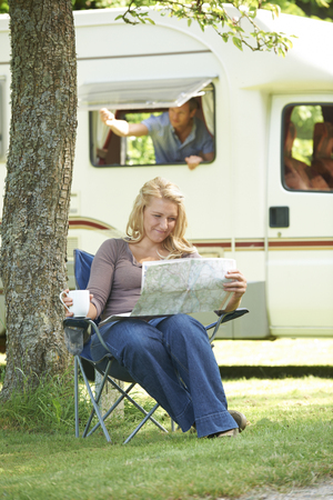 Woman Relaxing Outside Mobile Home On Vacation