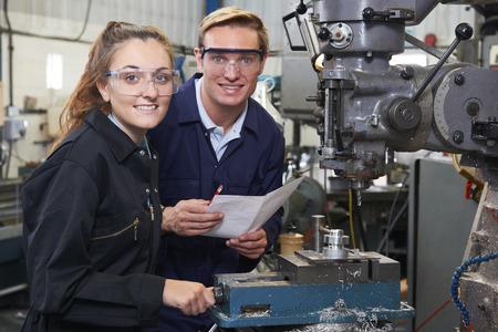 Retrato de ingeniero aprendiz mostrando cómo utilizar el taladro en la fábrica. Foto de archivo