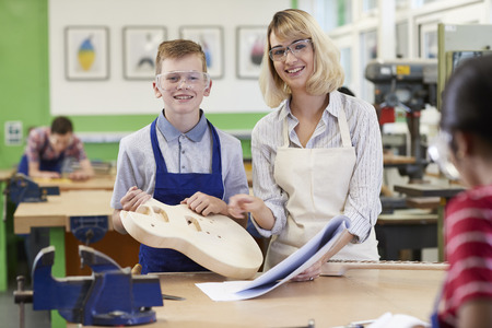 Portrait Of Female Teacher Helping Male High School Student Building Guitar In Woodwork Lesson 写真素材