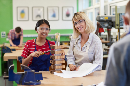 Portrait Of Teacher Helping Female High School Student Building Lamp In Woodwork Lesson Stock Photo