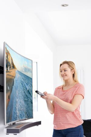 Young Woman With New Curved Screen Television At Home Stock Photo