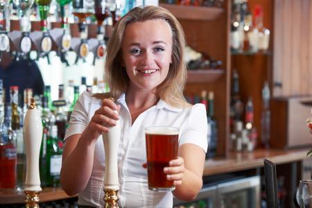 Female Bartender Serving Beer Behind Counter 版權商用圖片