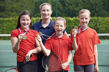 Portrait Of Winning Female School Tennis Team With Medals