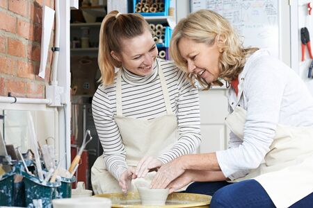 Mature Woman With Teacher In Pottery Class
