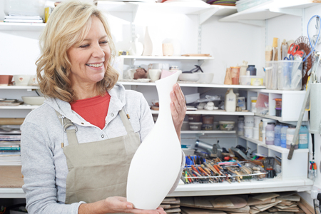 Reife Frau mit Vase im Töpferstudio