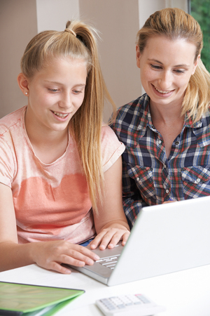 Female Home Tutor Helping Girl With Studies Using Laptop Stock Photo