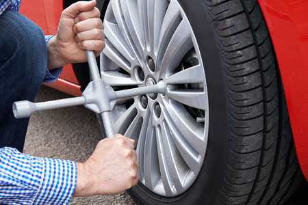 Close Up Of Man With Tyre Iron Changing Car Wheel