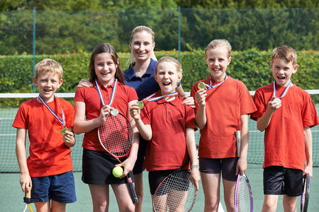 Portrait Of Winning School Tennis Team With Medals Stock Photo