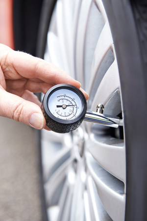 Close-Up Of Man Checking Car Tyre Pressure With Gauge Stock Photo