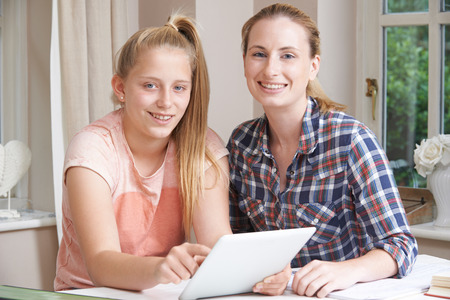 Female Home Tutor Helping Girl With Studies Using Digital Tablet At Camera