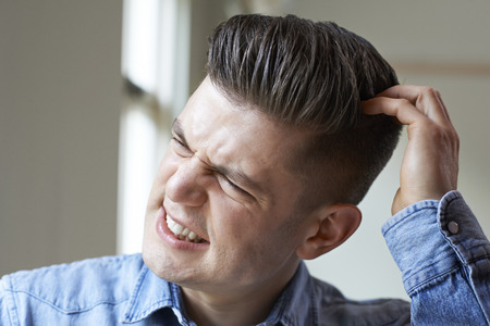 Shot Of Young Man Itching Scalp Stock Photo