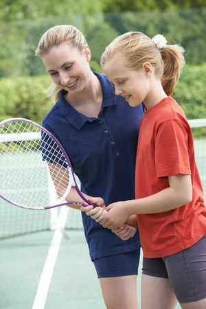 Female Tennis Coach Giving Lesson To Girl
