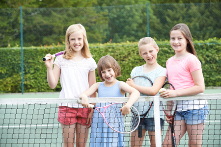 Portrait Of Group Of Girls Playing Tennis On Court