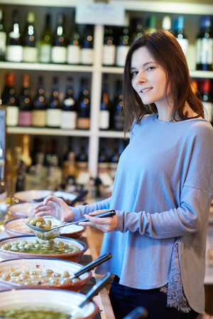 Portrait Of Female Customer In Delicatessen Filling Pot With Green Olives Stock fotó