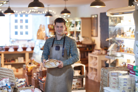 Portrait Of Smiling Male Owner Of Delicatessen Shop Wearing Apron Holding Loaf Of Bread