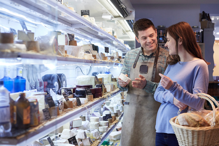 Männlicher Verkaufsassistent berät weibliche Kunden beim Einkaufen von Käse für Feinkost Standard-Bild