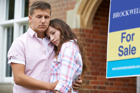 Young Couple Forced To Sell Home Through Financial Problems Standing Outdoors Next To For Sale Sign