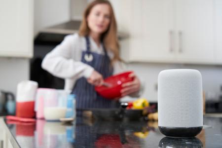 Vrouw bereidt maaltijd thuis die digitale assistent vraagt Stockfoto