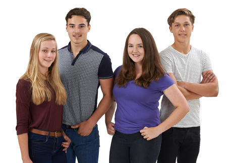 Studio Portrait Of Group Of Teenage Friends Standing Against White Background