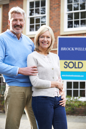 Portrait Of Mature Couple Standing Outside Dream Home Wit Sold Sign