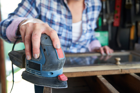 Close Up Mature Woman Upcycling Furniture In Workshop At Home Using Electric Sander