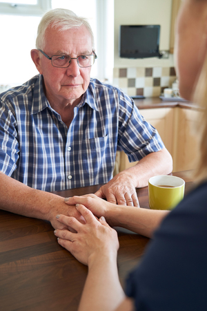 Woman Comforting Unhappy Senior Man Sitting In Kitchen At Home 免版税图像