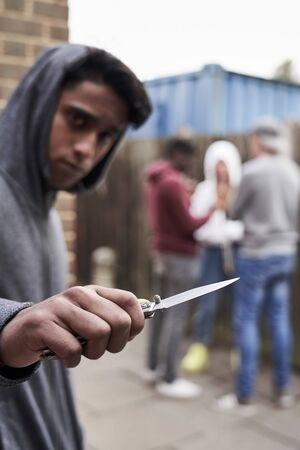 Teenage Boy In Urban Gang Pointing Knife Towards Camera Stock Photo