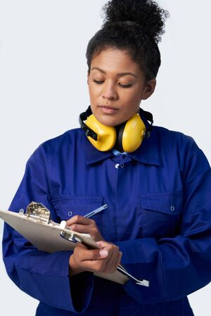 Studio Shot Of Female Engineer With Clipboard And Spanner Against White Background