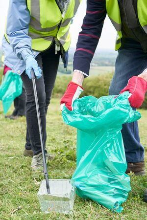 Close Up Of Helpful Senior Couple Collecting Litter In Countryside