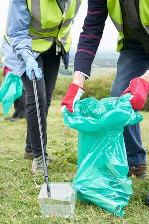 Nahaufnahme eines hilfreichen älteren Paares, das Müll in der Landschaft sammelt?