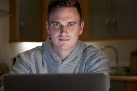 Portrait Of Suspicious Looking Man Using Laptop In Evening At Home