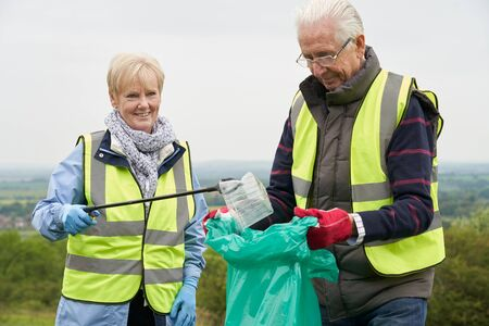 Helpful Senior Couple Collecting Litter In Countryside