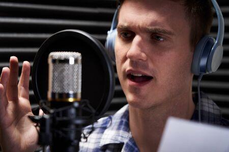 Man In Recording Studio Talking Into Microphone Stock Photo