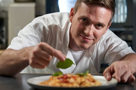 Portrait Of Male Chef Garnishing Plate Of Food In Professional Kitchen Imagens - 127607351