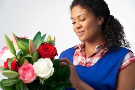 Studio Shot Of Female Florist Arranging Bouquet Of Lillies And Roses Against White Background