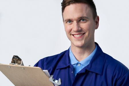 Studio Portrait Of Male Engineer With Clipboard And Spanner Against White Background Фото со стока