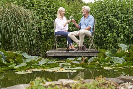 Mature  Couple Celebrating With Champagne Sitting On Chairs On Wooden Jetty By Lake