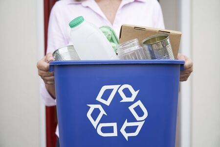 Close Up Of Woman Holding Recycling Bin Of Reusable Waste Outside Front Door Фото со стока
