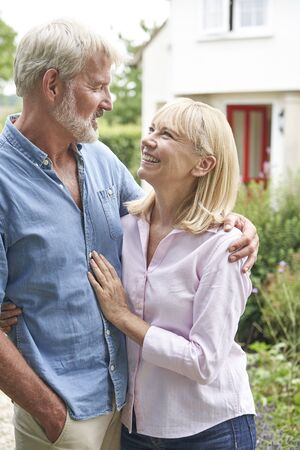 Mature Couple Standing In Garden In Front Of Dream Home In Countryside