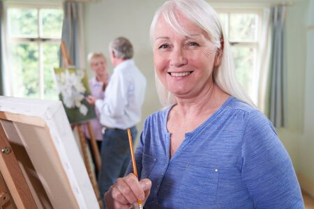 Portrait Of Seniors Woman Attending Painting Class With Teacher  In Background
