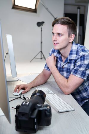 Male Photographer In Studio Reviewing Images From Photo Shoot On Computer Фото со стока