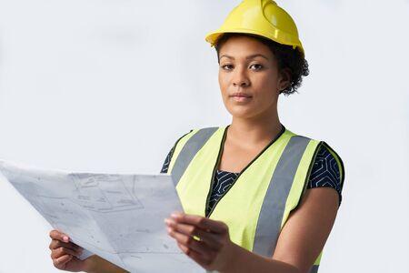 Studio Portrait Shot Of Female Architect Studying Plans Against White Background