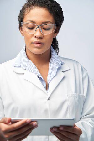 Studio Shot Of Female Laboratory Technician Working With Digital Tablet