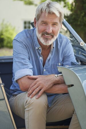 Portrait Of Proud Mature Man Sitting In Restored Classic Sports Car Outdoors At Home Фото со стока