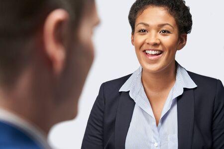 Studio Shot Of Businesswoman Interviewing Businessman For Employment Against White Background