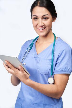 Studio Portrait Shot Of Female Nurse Wearing Scrubs Using Digital Tablet Фото со стока