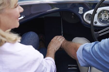 Close Up Of Loving Mature Couple Holding Hands On Road Trip In Classic Open Top Sports Car