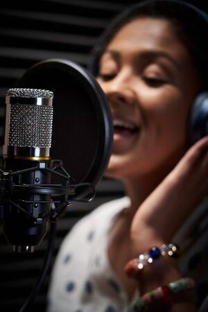 Female Vocalist Wearing Headphones Singing Into Microphone In Recording Studio Фото со стока
