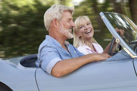 Couple d'âge mûr profitant d'un voyage sur la route en voiture de sport à toit ouvert classique ensemble